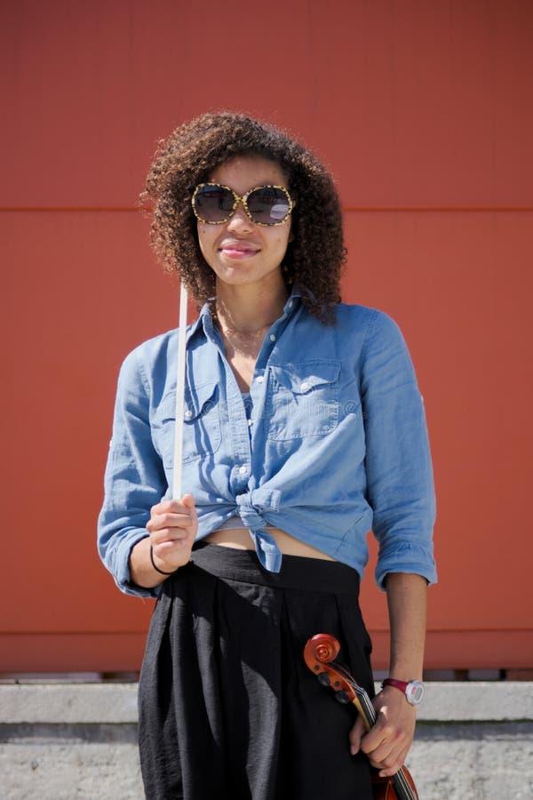 Violinista fêmea novo que guarda óculos de sol vestindo do instrumento imagem de stock
