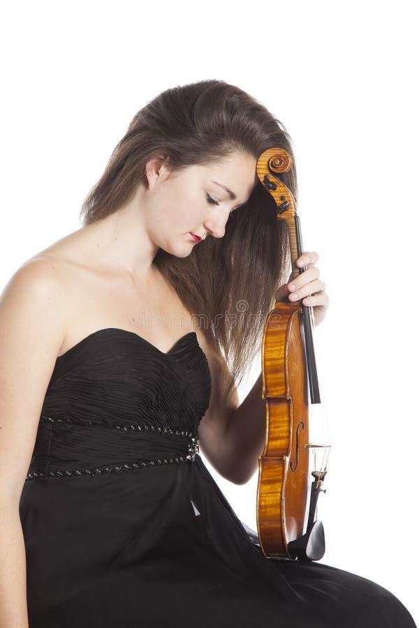 Violinista fêmea pensativo no vestido preto contra o fundo branco fotografia de stock