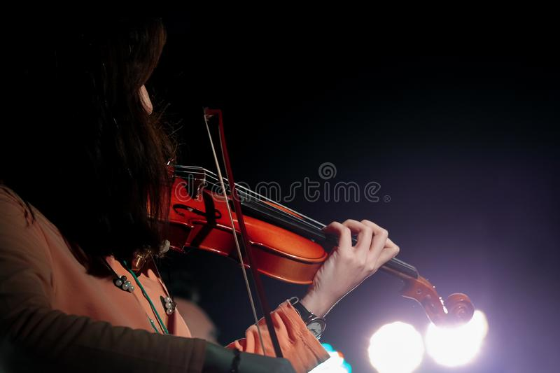 Violinista novo Girl Performance com seu instrumento do violino na fase interna do concerto foto de stock royalty free