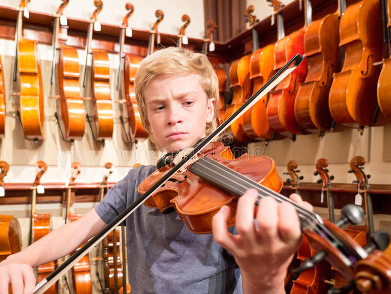 Violinista Playing del ragazzo un violino in Music Store fotografia stock libera da diritti