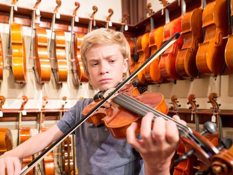 Violinista Playing do menino um violino em Music Store foto de stock royalty free