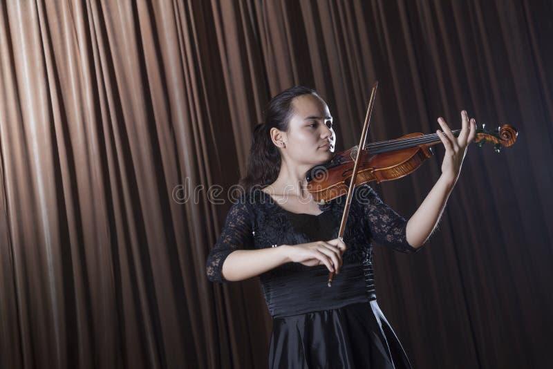 Violinista que está e que joga o violino em um desempenho foto de stock