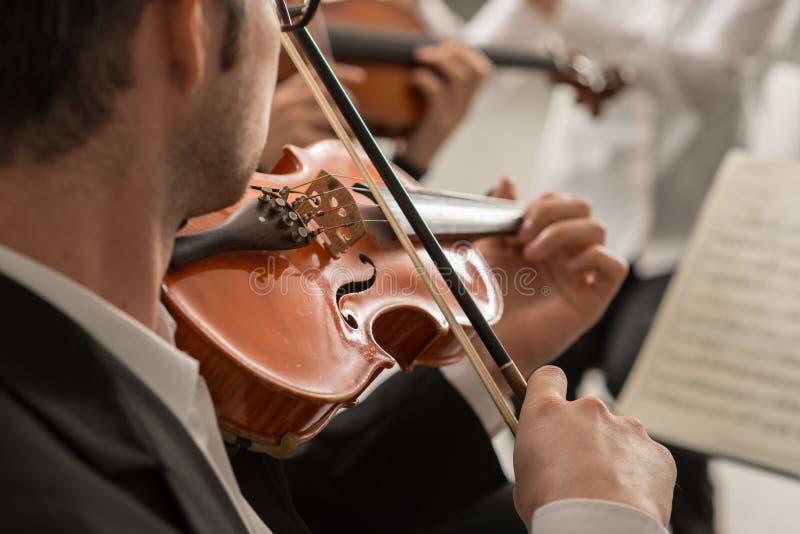 Violinista que executa na fase com a orquestra imagem de stock