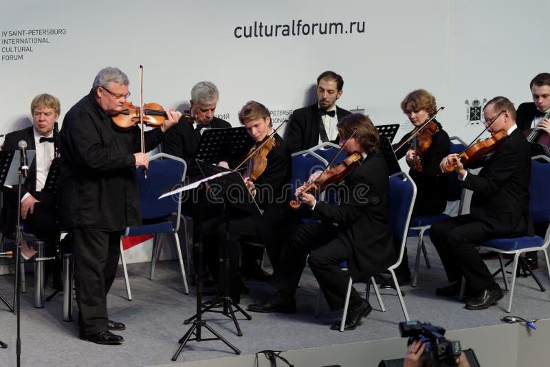 Violinista y conductor Sergey Stadler y la orquesta sinfónica de St Petersburg foto de archivo