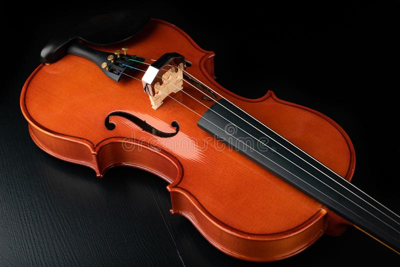 Violino brilhante novo bonito em uma tabela escura Instrumento musical da corda preparado para o trabalho foto de stock