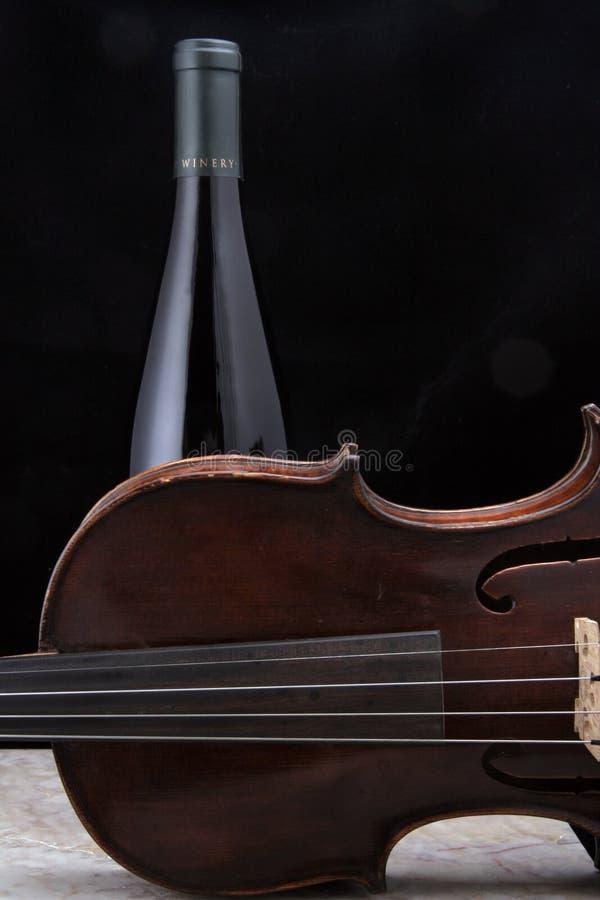 Violino com o frasco de vinho na telha fotos de stock