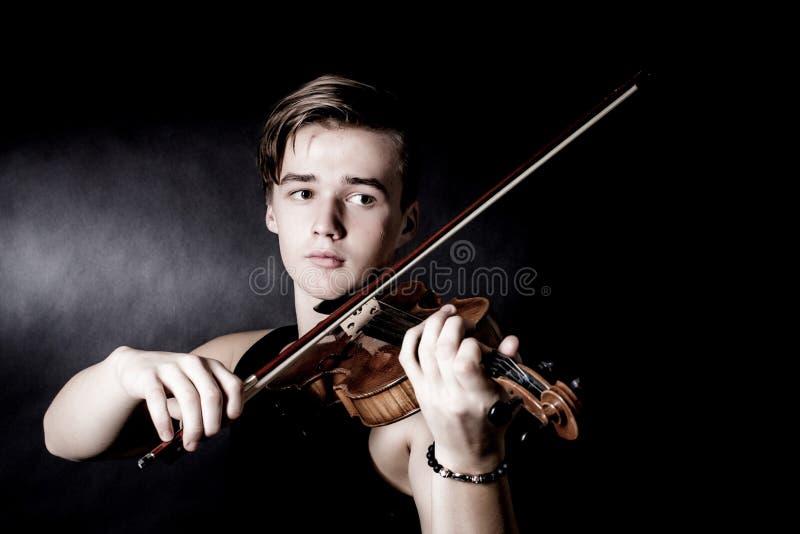 Violino del gioco del giovane su fondo scuro fotografie stock