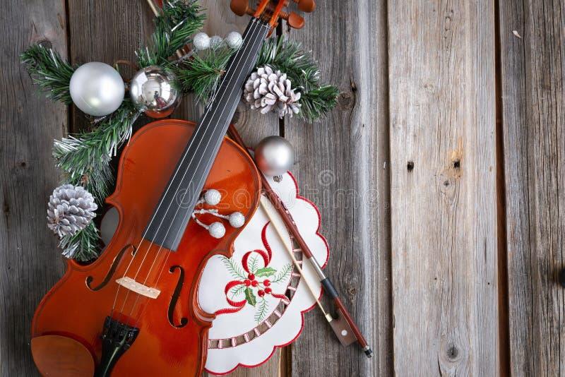 Violino e curva decorados com as bolas do Natal no fundo de madeira fotos de stock royalty free