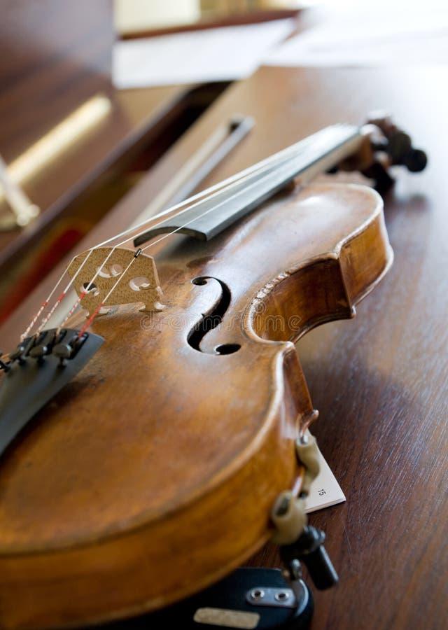 Violino no piano, luz traseira imagem de stock