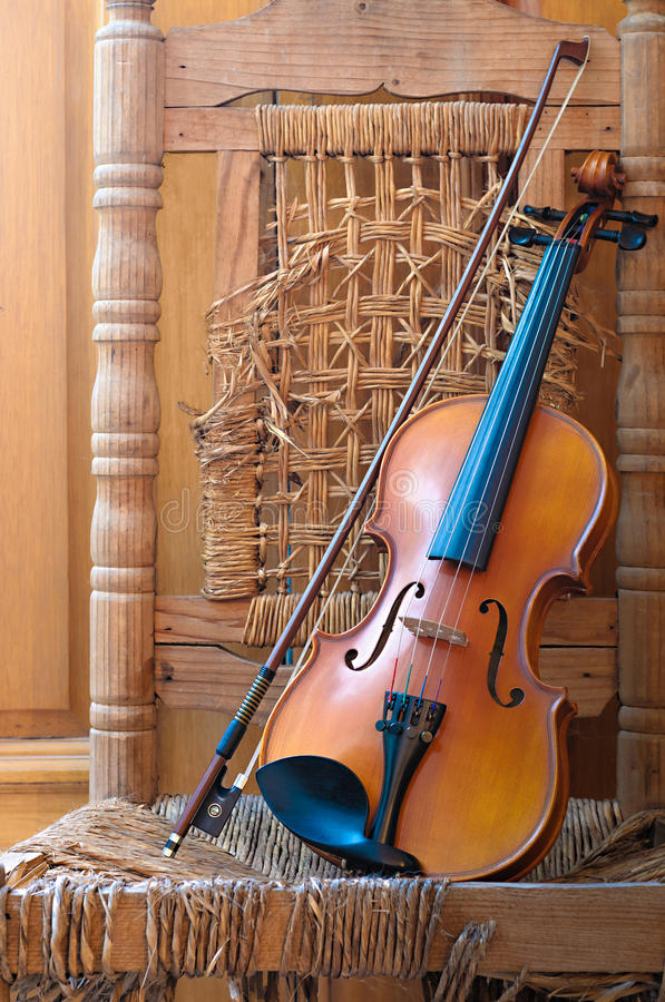 Violino que encontra-se em uma cadeira velha e arruinada fotografia de stock royalty free