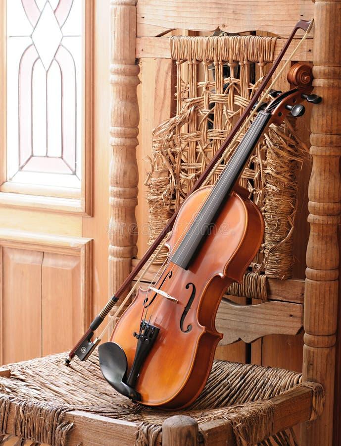 Violino que encontra-se em uma cadeira velha e arruinada fotos de stock