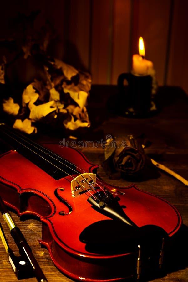 Violino, vela ardente e folhas de outono na tabela imagens de stock