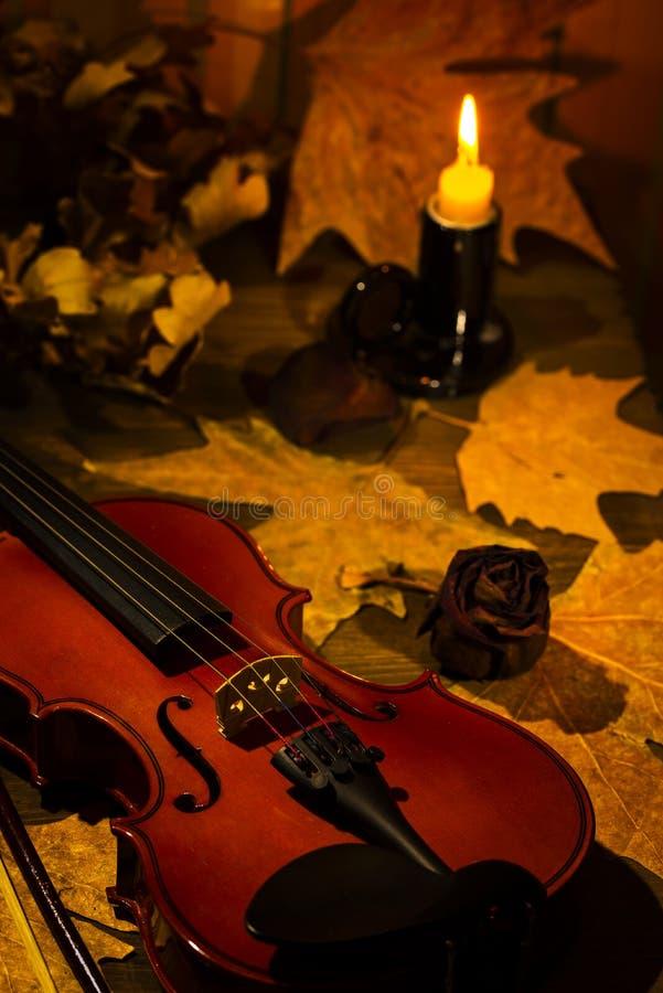 Violino, vela ardente e folhas de outono na tabela foto de stock