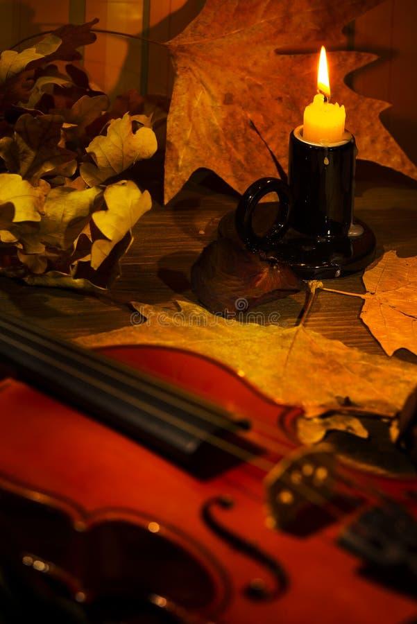 Violino, vela ardente e folhas de outono na tabela foto de stock royalty free