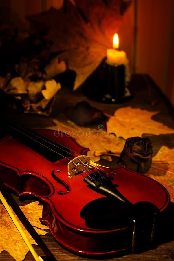 Violino, vela ardente e folhas de outono na tabela fotos de stock