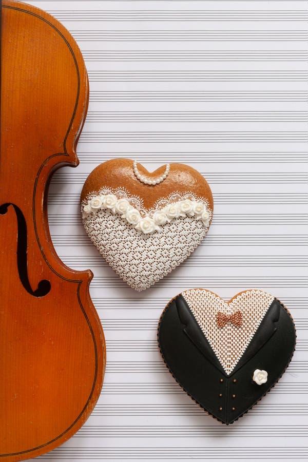 Violino velho e duas estatuetas da forma do coração do pão-de-espécie Noiva e noivo A vista superior, perto acima, coloca horizon fotos de stock royalty free