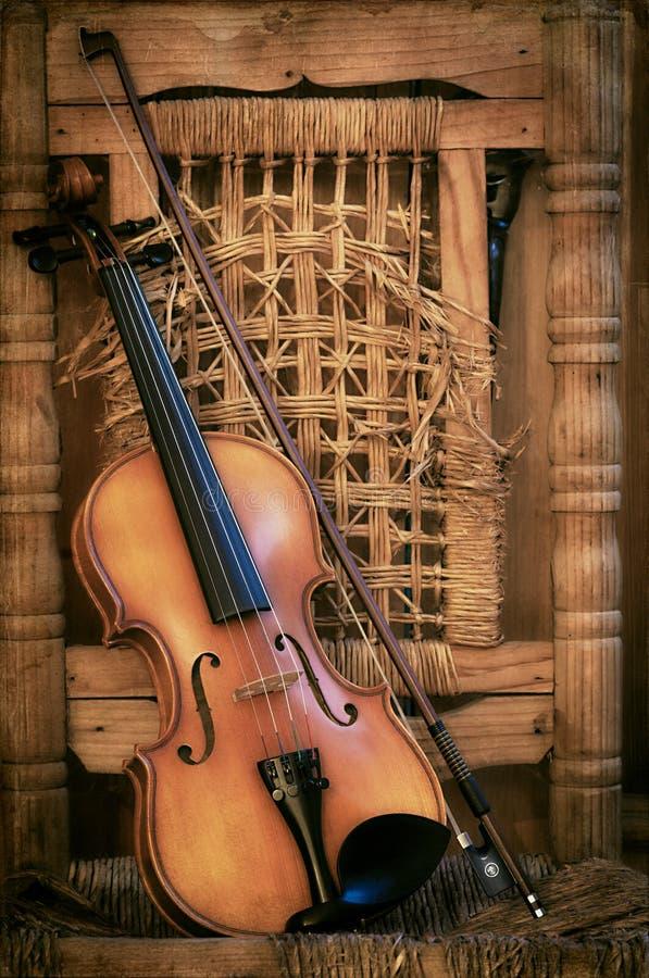 Violino velho que encontra-se em uma cadeira arruinada imagem de stock royalty free