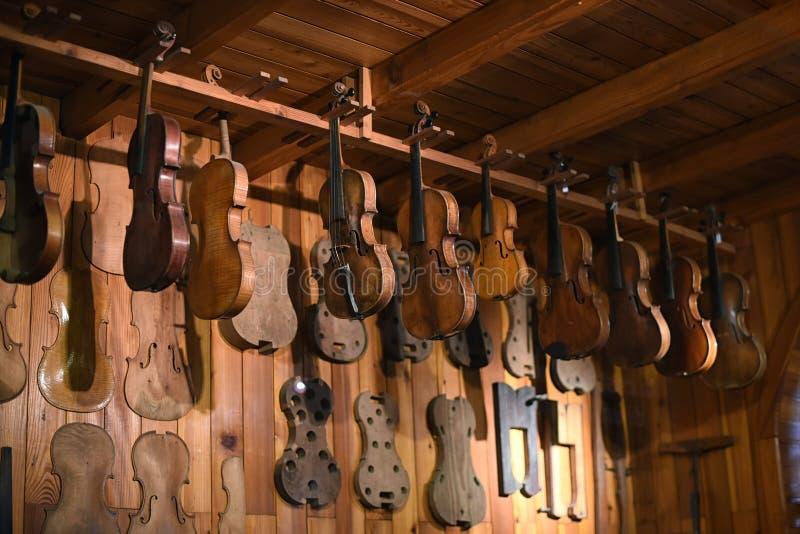 Violinos que penduram na oficina mais luthier imagens de stock royalty free