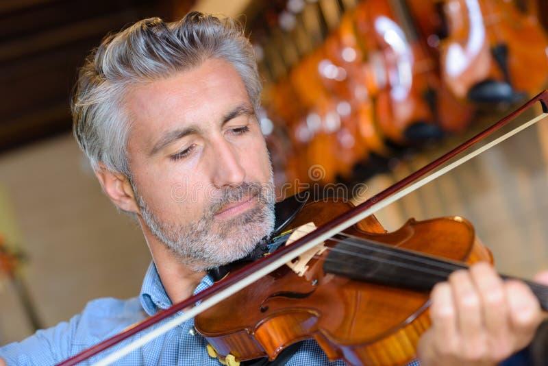 Violist die viool in muziekwinkel uitproberen stock afbeelding