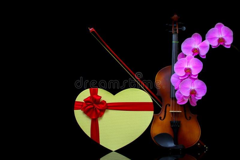 Violon avec arc, boîte cadeau en forme de coeur et orchidées roses sur fond sombre photos libres de droits