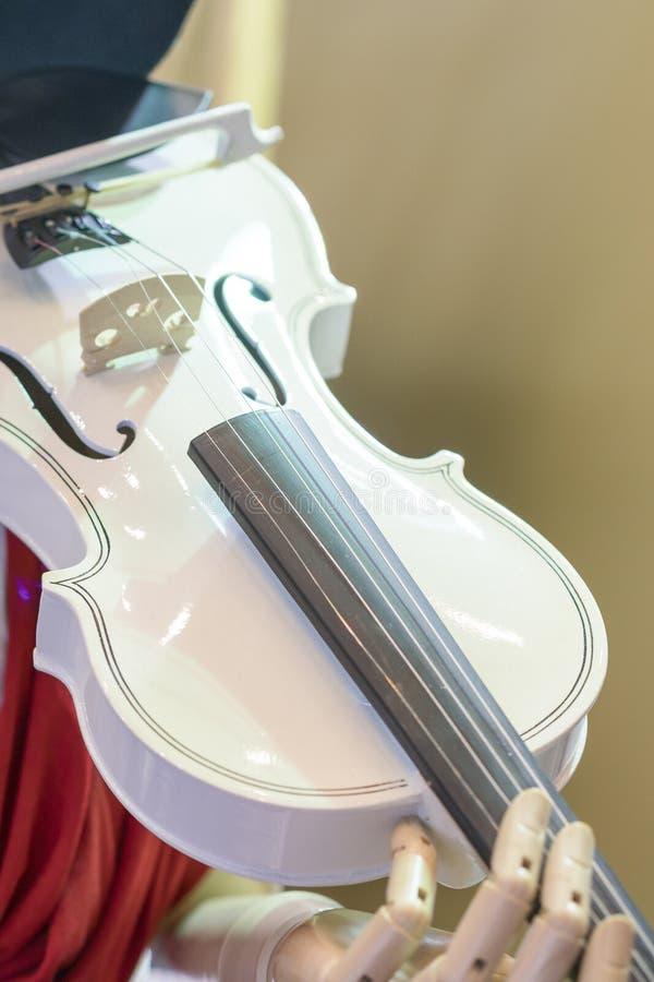 Violon blanc dans les mains d'un robot Le robot jouant le violon Photo verticale photo stock