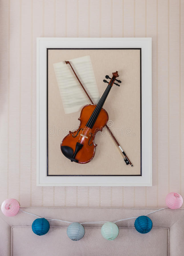 Violon with fiddlestick decoration on wall. In bedroom royalty free stock image