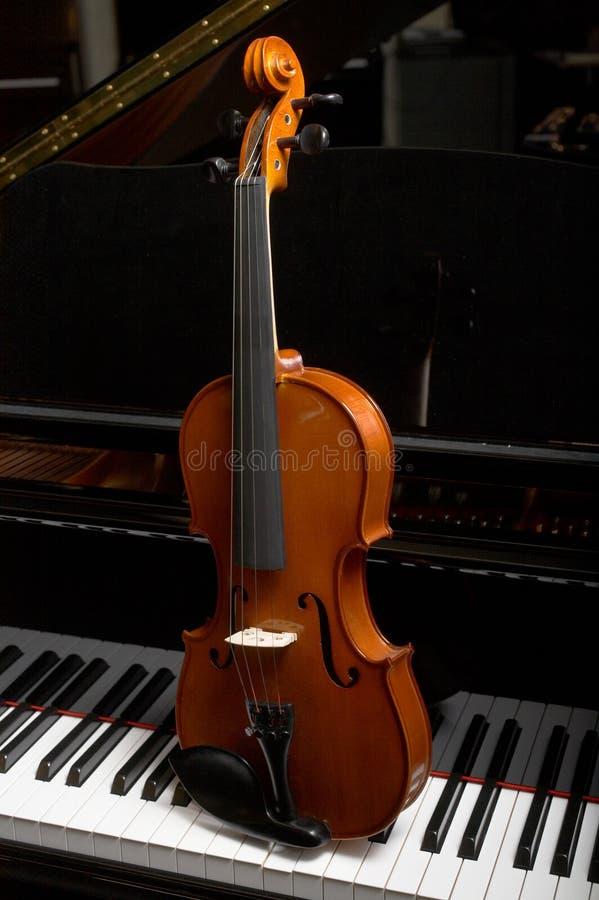 Violon sur des clés de piano photographie stock