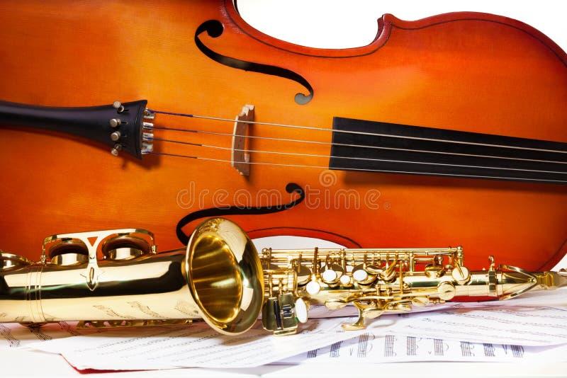 Violoncel en altsaxofoon op muzieknoten royalty-vrije stock afbeelding