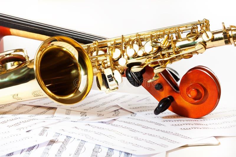 Violoncell som trimmar pinnor och den skinande guld- alt- saxofonen arkivbild