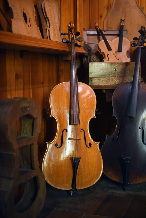 Violoncelles se tenant dans l'atelier luthier photographie stock libre de droits