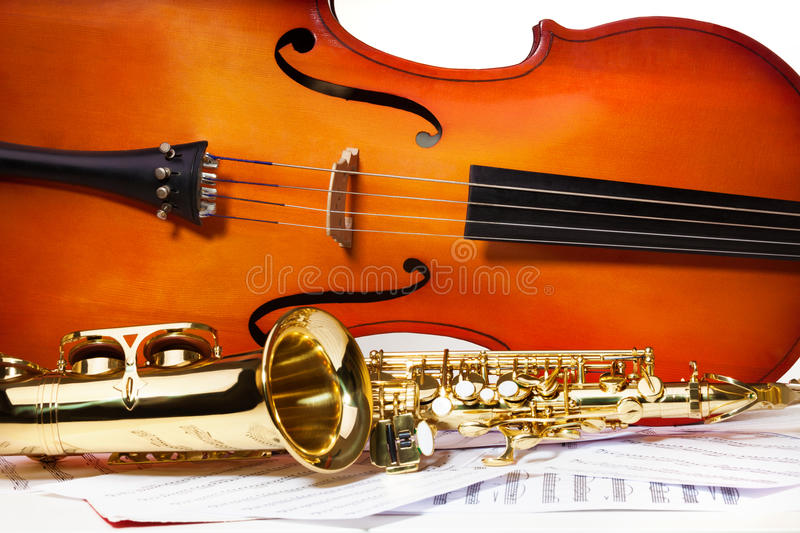 Violoncello and alto saxophone on musical notes. Violoncello and alto saxophone horizontally on the white paper with standard scales exercises royalty free stock image