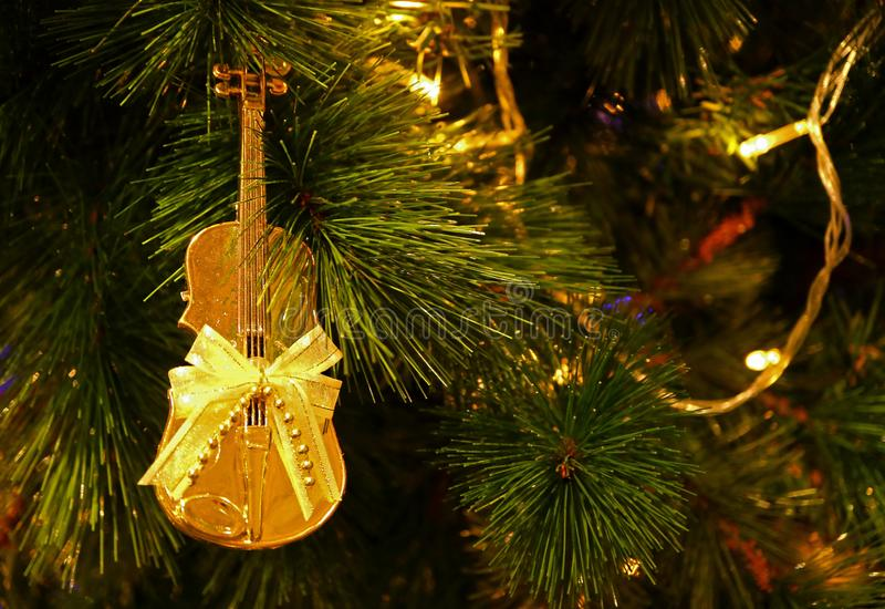 Violoncelo brilhante do ouro dado forma com o ornamento do Natal da curva da fita que pendura na árvore de Natal efervescente foto de stock royalty free