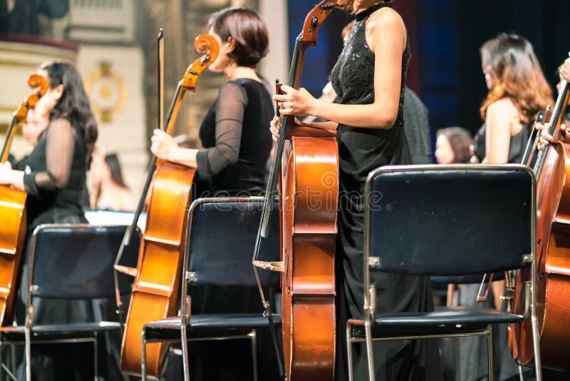 Violoncelo en manos del violoncelista en el primer del concierto de la sinfonía de la música clásica imágenes de archivo libres de regalías