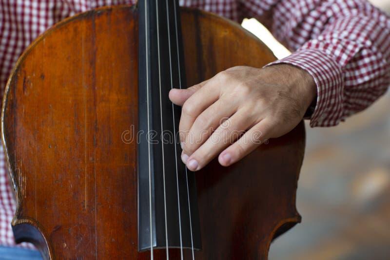 Violoncelo que joga as mãos do violoncelista perto acima dos instrumentos da orquestra imagem de stock royalty free