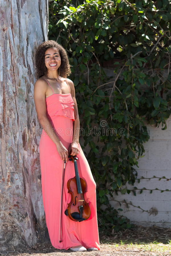 Violoniste féminin de sourire dans la longue robe rose dehors photographie stock