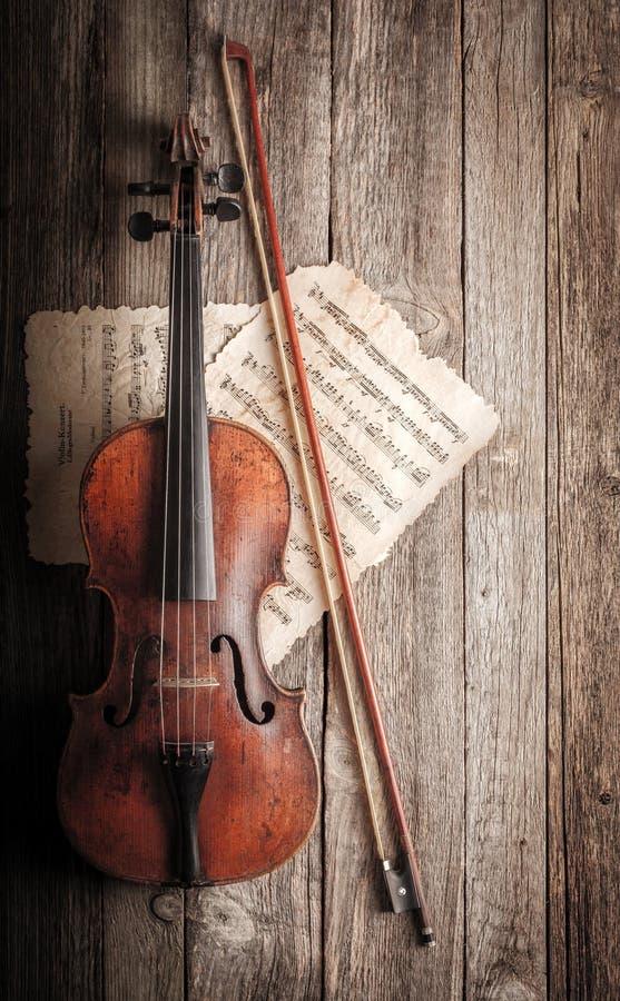Viool, boog en muzikale score op houten achtergrond royalty-vrije stock fotografie