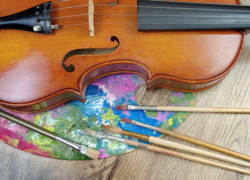Viool, borstels en palet op een houten achtergrond stock afbeeldingen