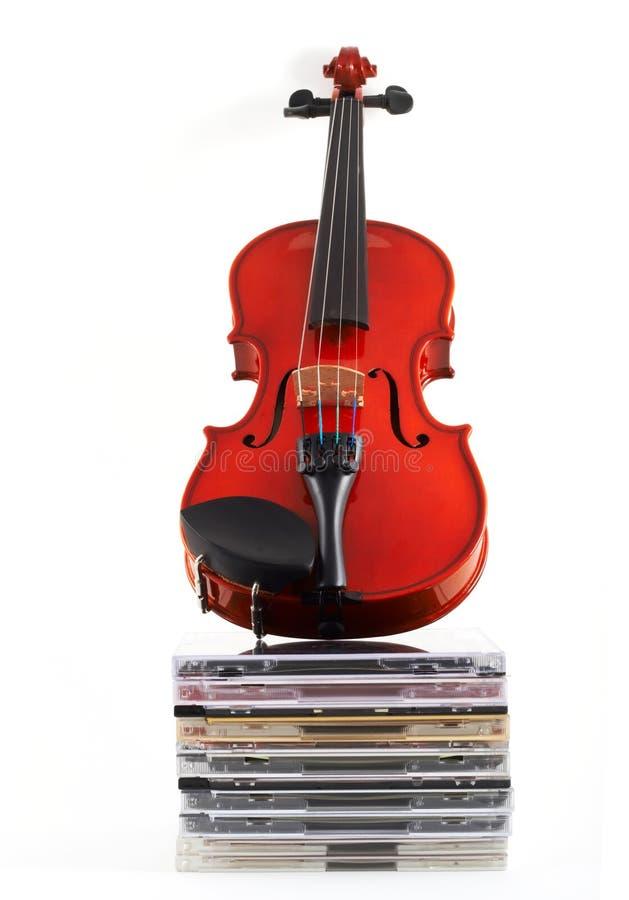 Viool die zich rechtop op CDs bevindt royalty-vrije stock afbeelding