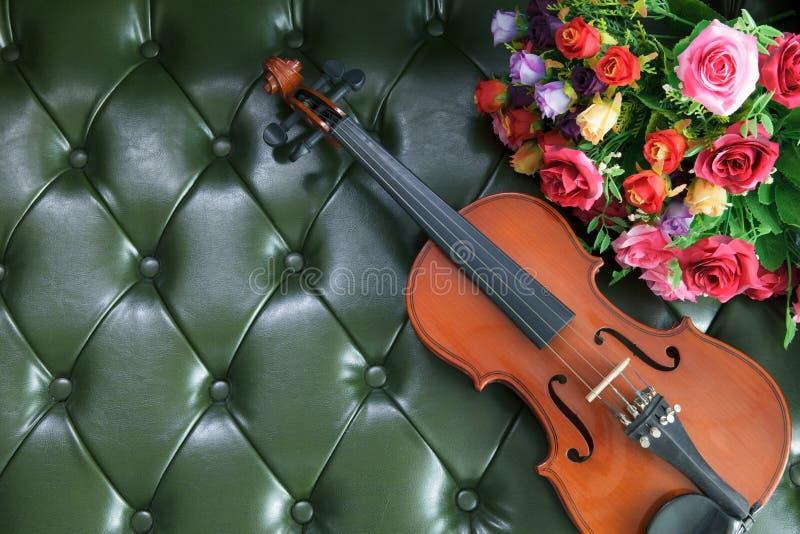 Viool en bloem op backgrou van het luxe groene leer stock afbeelding