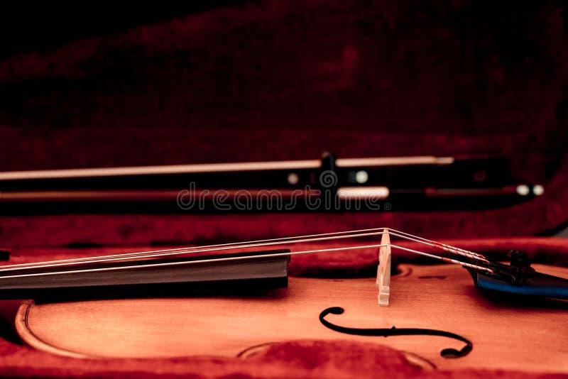 Viool en boog in donkerrood geval Sluit omhoog mening van een vioolkoorden en brug royalty-vrije stock fotografie