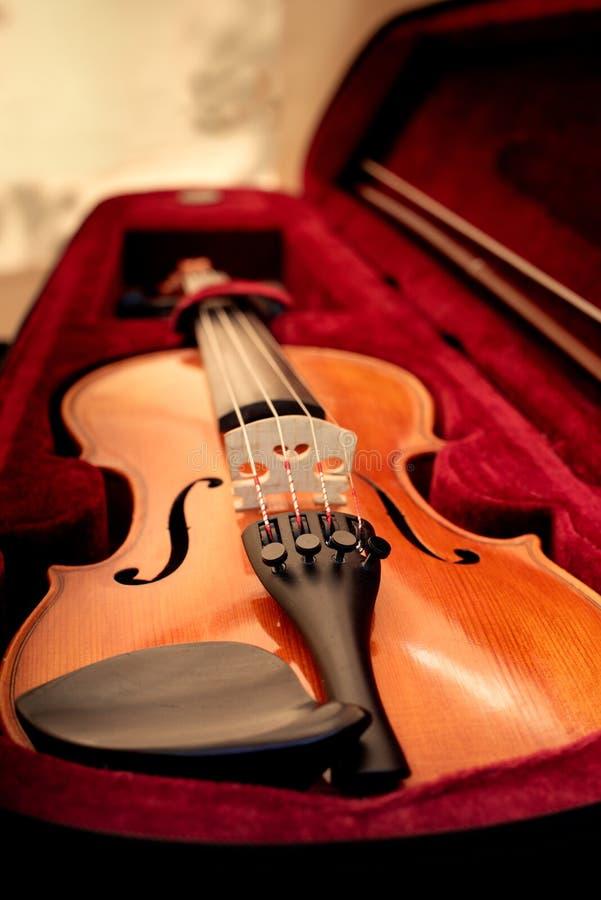Viool en boog in donkerrood geval Sluit omhoog mening van een vioolkoorden en brug royalty-vrije stock afbeeldingen