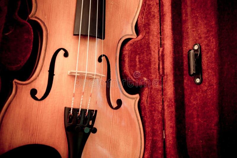 Viool en boog in donkerrood geval Sluit omhoog mening van een vioolkoorden en brug stock foto's