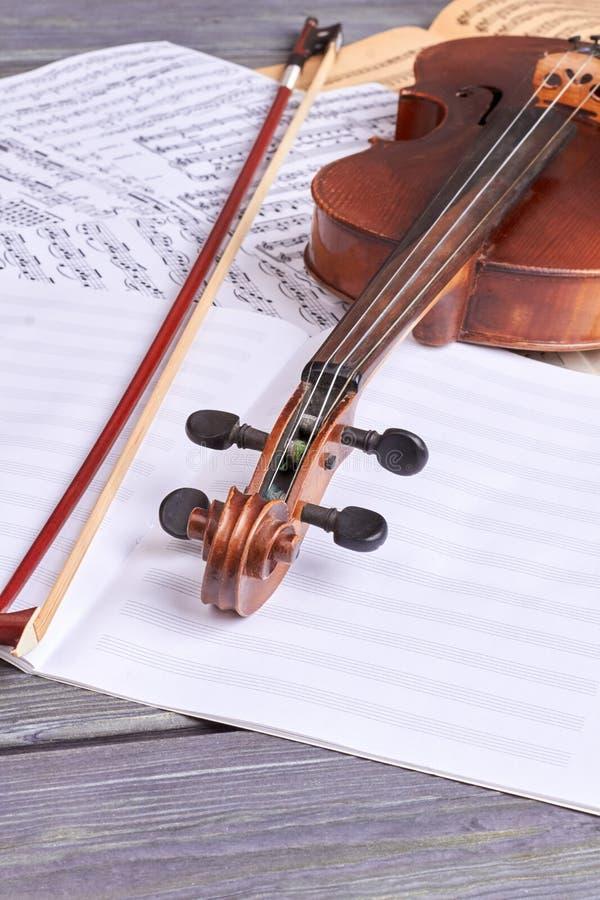 Viool en muzieknoten op houten achtergrond stock afbeelding