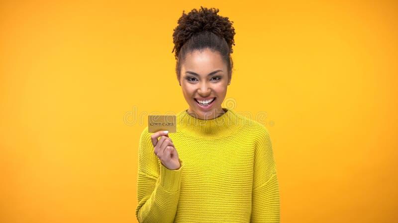 黑人妇女藏品金黄信用卡,开户有钱人的VIP节目 免版税库存图片