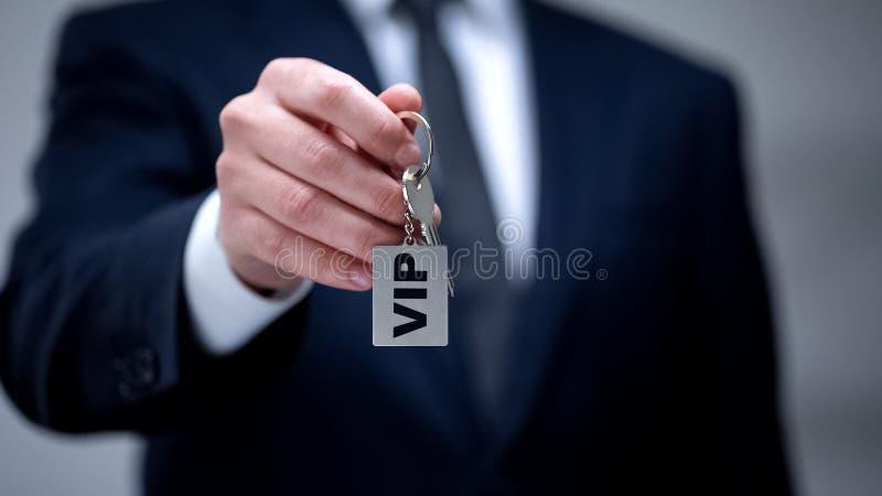 VIP woord op keychain in mannelijke hand, luxeaanpassing voor zakenreis royalty-vrije stock foto