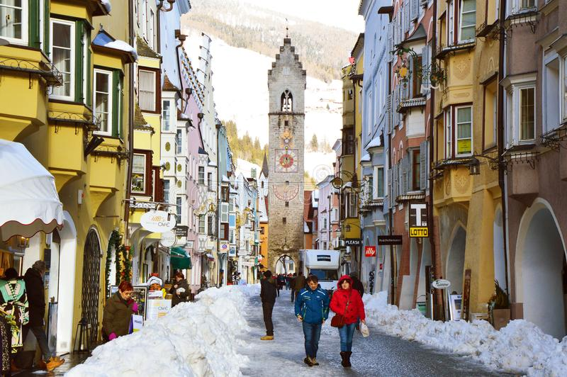 VIPITENO, ITALY - JANUARY 23, 2018: Zwölferturm tower and people in main street of the old medieval town of Vipiteno. Sterzing, South Tyrol, Italy stock photography