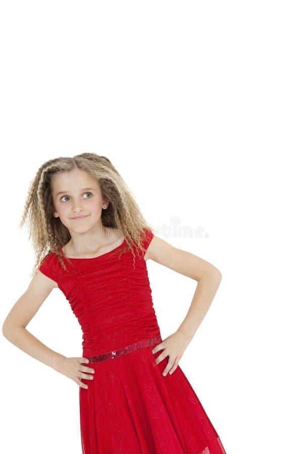 Vippa på bilden av flickan som bär den röda munkkåpan som från sidan ser med händer på höfter över vit bakgrund arkivbild