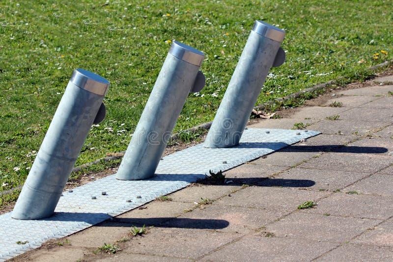 Vippade på metallpoler som används för att parkera och uppladdning av hyrda elektriska cyklar som monteras på den omgivna metalls fotografering för bildbyråer