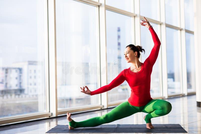 Virabadrasana. Beautiful yoga woman practice in a big window. Hall background. Yoga concept stock photo