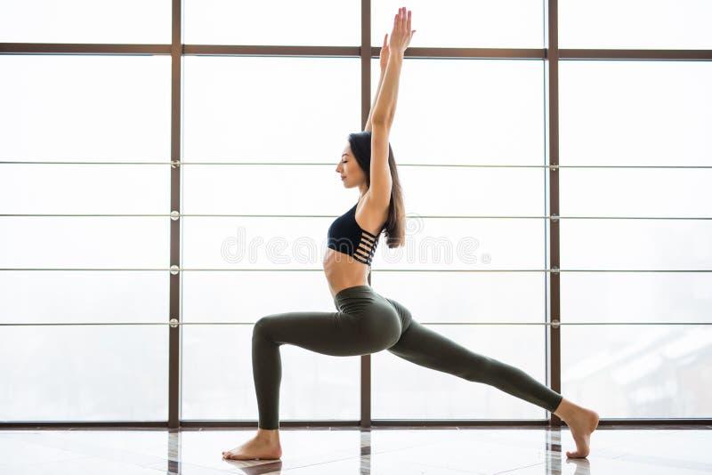 Virabhadrasana Beautiful yoga woman practice near window yoga room studio background. Yoga concept. stock images